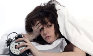 young woman woman in bed awakening tired holding alarm clock on white background